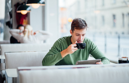 태블릿 컴퓨터를 사용하는 동안 젊은 남자가 거리에서 커피를 마시는