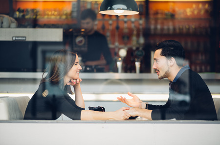 Couple in love drinking coffee laughing in coffee shop