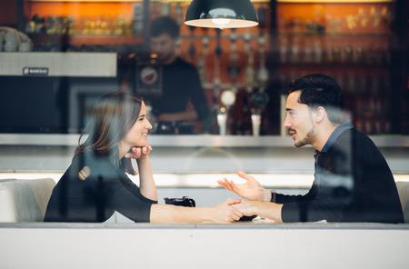 Paar in liefde het drinken van koffie lachen in coffeeshop