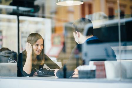 dattes: Jeunes couples parlant � caf� Banque d'images