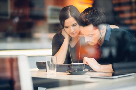 Paar met behulp van tablet-computer in de coffeeshop Stockfoto