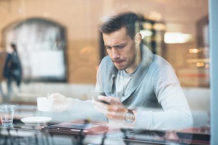 젊은 남자가 카페에서 커피를 마시고 전화를 사용 스톡 콘텐츠