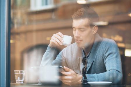 젊은 남자의 태블릿 컴퓨터를 사용하는 카페에서 커피를 마시는 스톡 콘텐츠