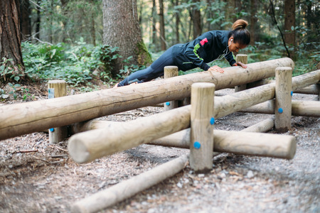 Young woman doing push ups in the woods photo