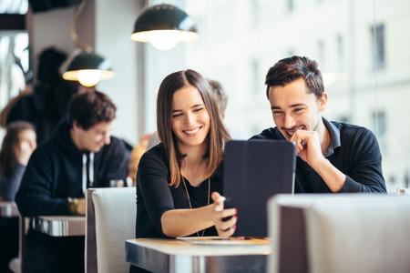 カフェで笑いながらタブレット コンピューターで写真を見て若いカップル