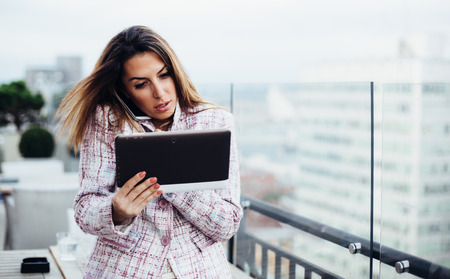 Young businesswoman talking on phone and using tablet computer in cafe photo