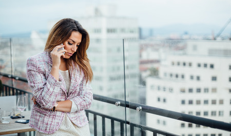 Young businesswoman talking on phone in cafe photo