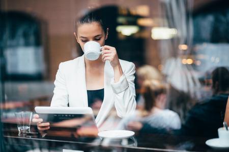 Jonge zakenvrouw drinken koffie en het gebruik van tablet-computer in cafe