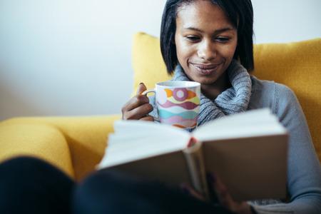 mujer leyendo libro: Mujer bebiendo té y leyendo el libro en el sofá