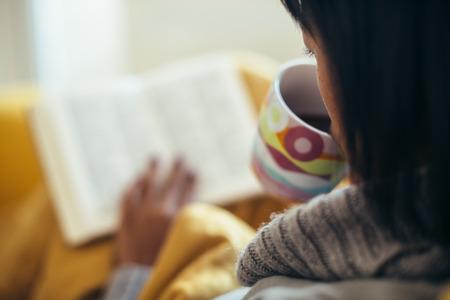 お茶を飲むと、ソファで本を読む女性