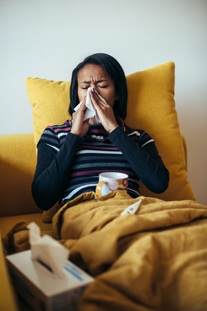 sick: Sick young woman blowing her nose on the sofa