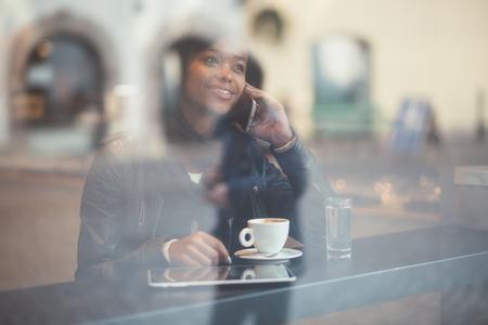 cafe internet: Mujer joven hablando por teléfono en la tienda de café Foto de archivo