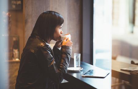Jonge vrouw het drinken koffie in de moderne cafe