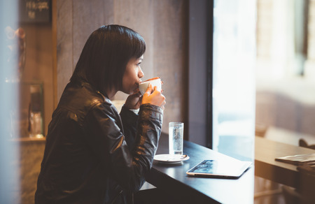 thinking woman: Young woman drinking coffee in modern cafe