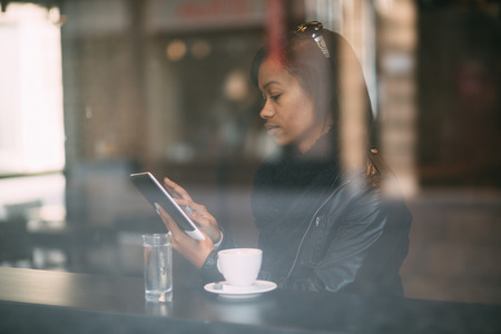 Young woman using tablet computer in coffee shop photo