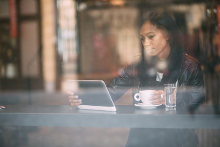若い女性のコーヒー ショップでタブレット コンピューターを使用して 写真素材