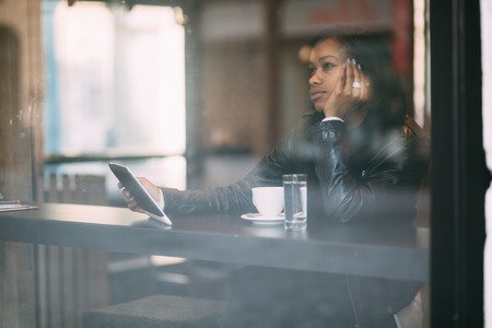 Young woman daydreaming in coffee shop photo
