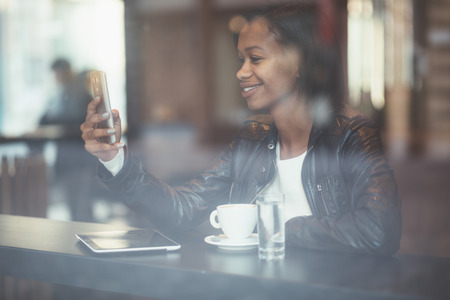 Young woman using phone in coffee shop photo