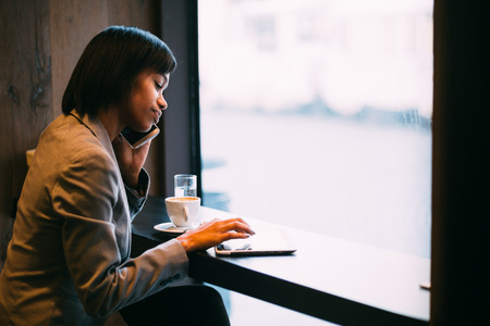 Young businesswoman talking on phone in coffee shop photo