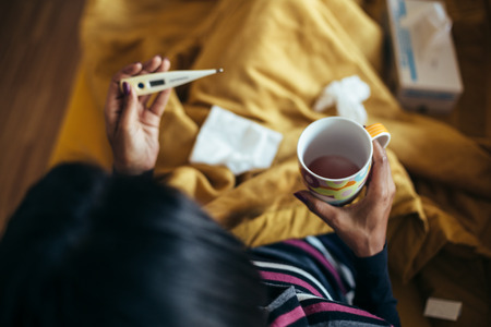 gripe: Enfermo mujer que beber té que sostiene el termómetro en el sofá