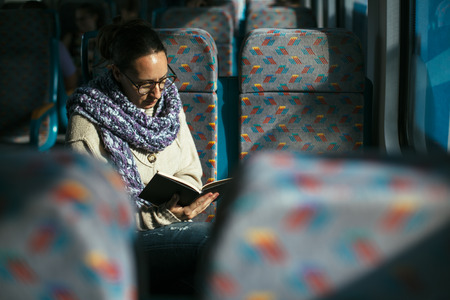 trains: Woman reading book on train bus