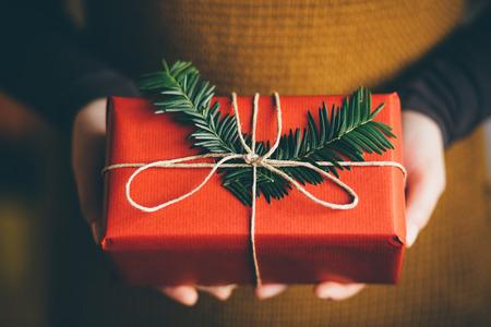 Woman holding modern Christmas present gift Imagens