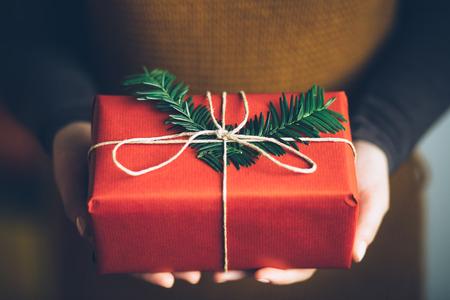 現代のクリスマスを保持している女性のギフトを示す 写真素材