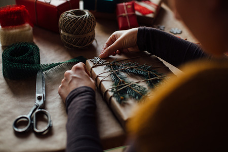 Woman wrapping modern Christmas gifts presents at home photo