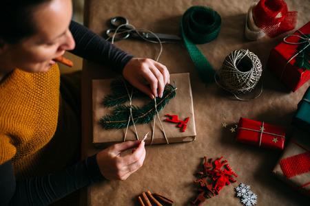 smoking cigar: Woman wrapping modern Christmas gifts presents at home Stock Photo