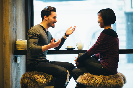 a couple: Interracial couple talking in coffee shop