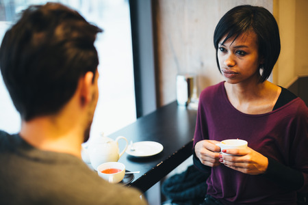 Interracial couple talking in coffee shop photo