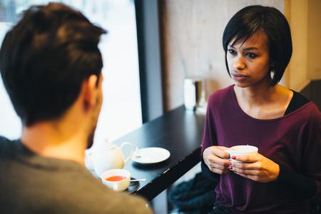 Interracial paar praten in coffeeshop Stockfoto