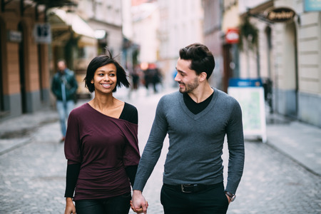 date: Interracial couple holding hands on the street Stock Photo
