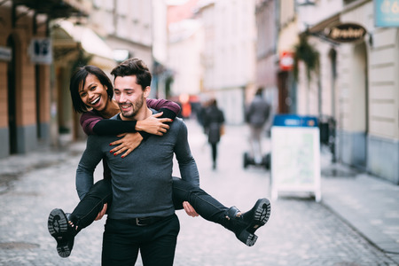 mixed race person: Young man giving girlfirend piggyback ride