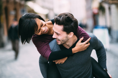embracing couple: Interracial couple in love having fun in the city