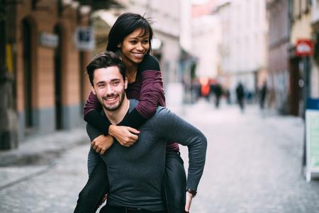parejas felices: Hombre joven que da a cuestas paseo girlfirend
