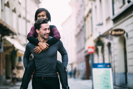 Young man giving girlfirend piggyback ride photo