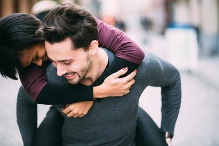 parejas romanticas: Pareja interracial en el amor que se divierte en la ciudad Foto de archivo