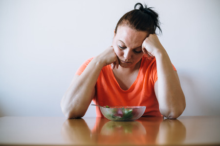 Unhappy overweight looking at salad. Diet concept.