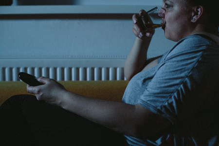 plus sized: Overweight woman watching TV drinking whiskey Stock Photo
