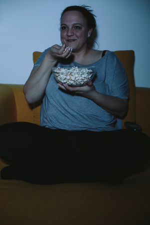 plus sized: Overweight woman watching horror movie on TV