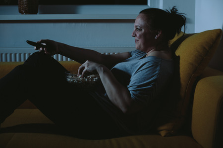 Overweight woman watching TV eating popcorn photo