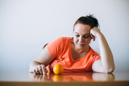 Unhappy overweight looking at orange. Diet concept.