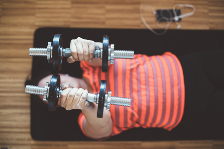 plus sized: Overweight woman lifting weights