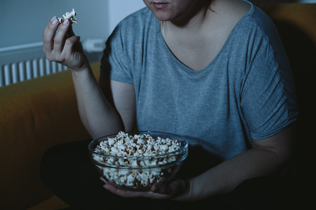 relaxed woman: Overweight woman watching TV eating popcorn