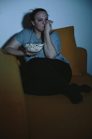 mujer viendo tv: Mujer con sobrepeso viendo la televisi�n comiendo palomitas de ma�z