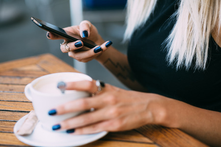 Close up of hip young woman using phone in cafe Stockfoto