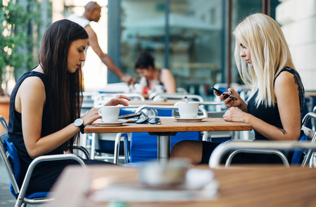A couple of modern day female friends using technology instead of talking to each other in cafe