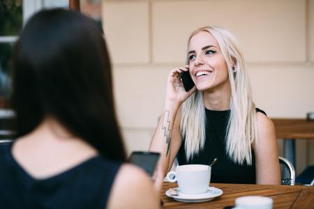 hablando por telefono: Mujeres jovenes que hablan en el teléfono en café al aire libre