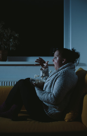 plus sized: Frightened overweight woman watching horror movie dropping popcorn
